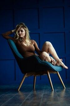 Schöne blondine kreuzte ihre beine auf dem sessel. sexy mädchen in verschiedenen posen auf einem grauen sessel in einem blauen raum.