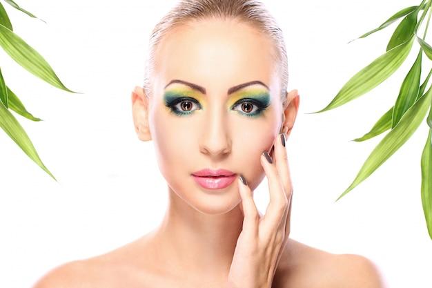 Schöne blondine mit bambusblättern