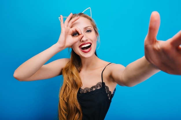 Schöne blondine mit katzenohren, die spaß an der partei haben, lächelnd, selfie nehmend. hat welliges langes haar. tragen eines schönen schwarzen kleides mit spitze, hellem make-up.