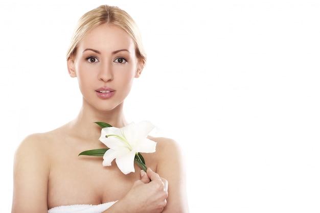 Schöne blondine mit lilienblume