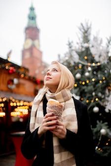 Schöne blondine mit spuckenkuchen am weihnachtsmarkt in breslau, polen