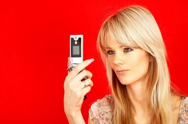 Schöne blondine mit telefon über rotem hintergrund
