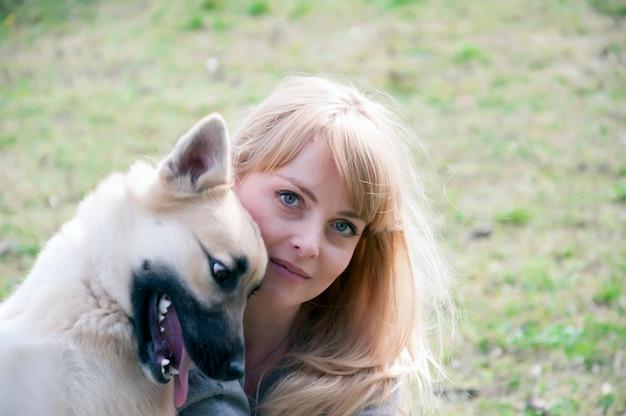 Schöne blondy frau, die mit hund in der natur während des herbsttages spielt.