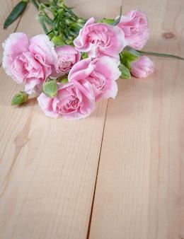 Schöne blühende gartennelkenblume auf einem hölzernen hintergrund