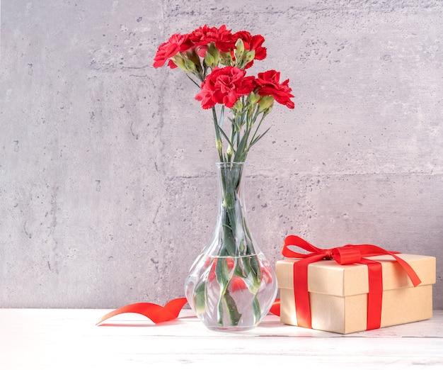 Schöne blühende nelken mit roter bandbox lokalisiert auf hellem grauem hintergrundschreibtisch, nahaufnahme, kopienraum