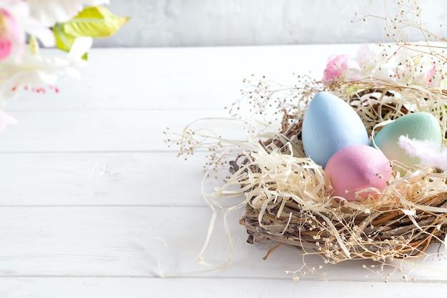 Schöne blume mit bunten eiern im nest auf hellem hintergrund
