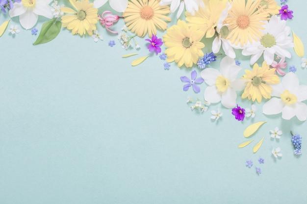 Schöne blumen auf blauer papieroberfläche