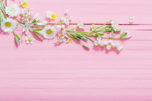 Schöne blumen auf rosa hölzernem hintergrund