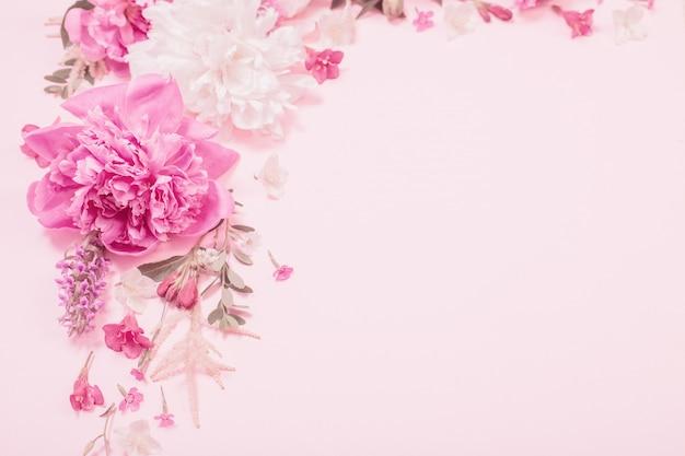 Schöne blumen auf rosa papierhintergrund