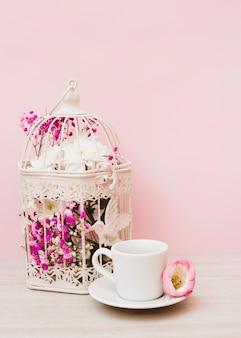 Schöne blumen im weißen käfig mit tasse und untertasse auf hölzernem schreibtisch gegen rosa hintergrund