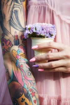 Schöne blumen in den händen eines mädchens mit tätowierungen