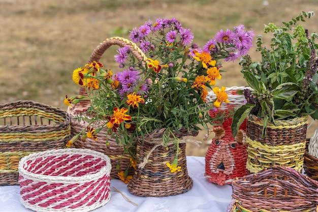 Schöne blumen in einer korbvase auf einem tisch, im freien, nahaufnahme. bouquet von violetten, lila und orangefarbenen blüten. dekoration des hauses. tapete und hintergrund. gartenarbeit der ukraine