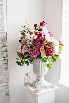 Schöne blumen in klassischer weißer vase. innendekoration, galerie.