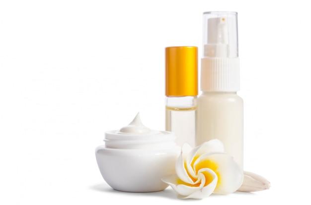 Schöne blumen und flaschen mit der natürlichen hautpflegecreme lokalisiert auf weiß