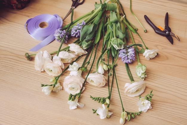 Schöne blumen und floristenausrüstung auf holztisch
