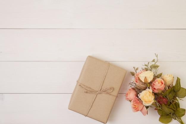 Schöne blumen- und geschenkbox auf hölzernem hintergrund mit romantischem