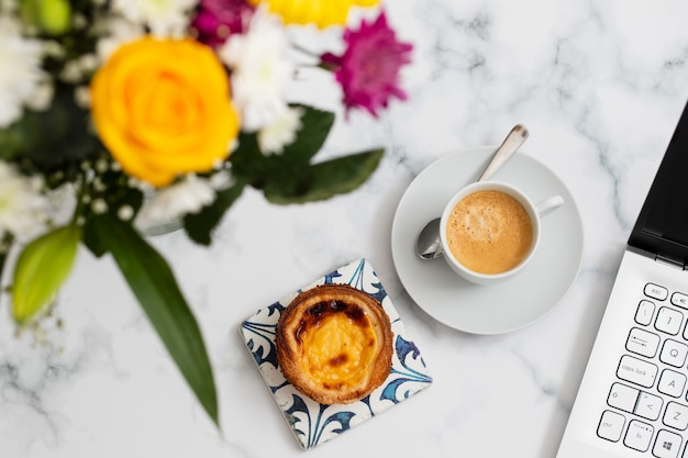 Schöne blumen und kaffee mit pastell de nata