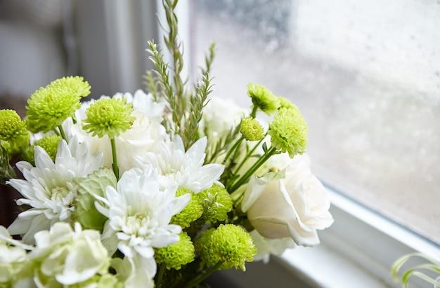 Schöne blumenkomposition mit weißen und grünen blumen nahe dem fenster