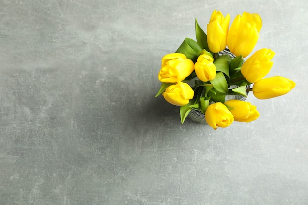 Schöne blumenstrauß-tulpen in der vase auf grauer draufsicht. platz für text