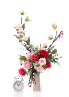 Schöne blumenstraußblume in der vase mit einer uhr auf weißem hintergrund