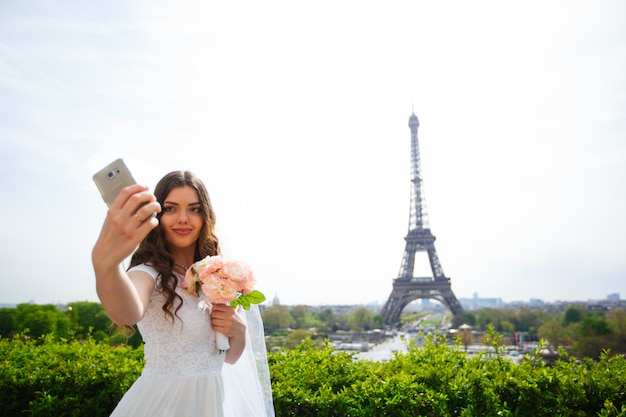 Schöne braut, die ein selfie in paris nimmt