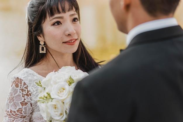 Schöne braut, die in die augen des bräutigams schaut, während blumenstrauß hält