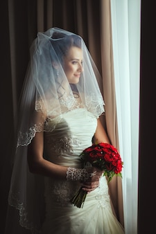 Schöne braut, die nahes fenster steht. das mädchen in einem weißen hochzeitskleid.