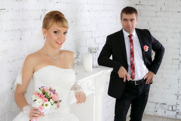 Schöne braut ein bräutigam an ihrem hochzeitstag nahe kamin