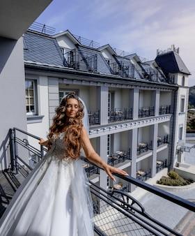 Schöne braut gekleidet im luxuriösen weißen kleid auf dem balkon einer wohnung am sonnigen tag