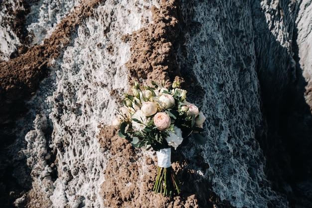 Schöne braut hält einen bunten blumenstrauß der hochzeit. schönheit der farbigen blumen. nahaufnahmebündel von röschen. brautaccessoires. weibliche dekoration für mädchen. details zur heirat und für ehepaare
