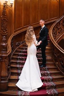 Schöne braut im hochzeitskleid mit schöner frisur und bräutigam im schwarzen anzug auf schönen holztreppen. halle. rückansicht.