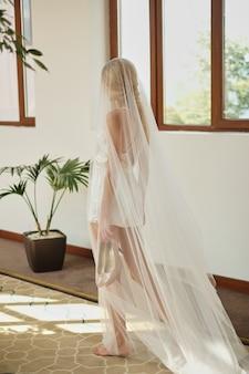 Schöne braut im weißen hochzeitskleid und im schleier, die auf bräutigam vor hochzeitszeremonie stehen,