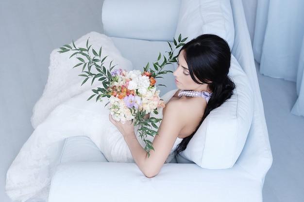 Schöne braut im weißen kleid, das einen blumenstrauß hält