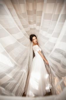 Schöne braut im weißen kleid, das unter vorhang aufwirft