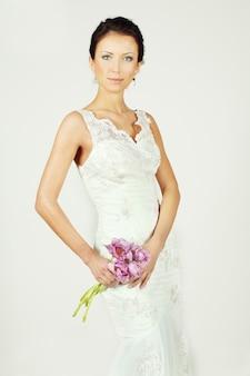 Schöne braut im weißen kleid mit blumenstrauß