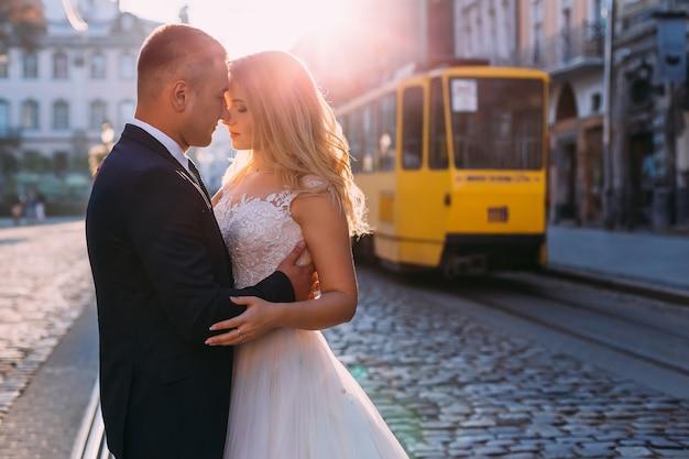 Schöne braut im weißen kleid mit spitze. der bräutigam im anzug umarmt die braut