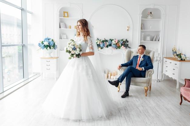Schöne braut im weißen kleid und im bräutigam im anzug, posierend im weißen studio-interieur, hochzeit