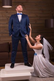 Schöne braut im weißen kleid und im schleier macht heiratsangebot zum bräutigam im anzug, der auf tisch auf holzraum steht