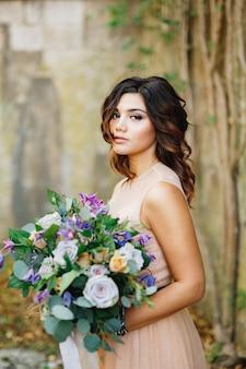 Schöne braut in einem cremefarbenen kleid mit einem strauß rosen in ihren händen