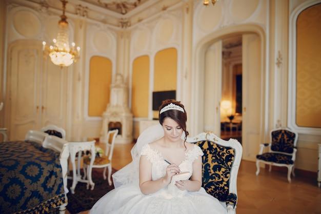 Schöne braut in einem herrlichen weißen kleid und eine krone auf dem kopf