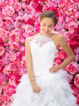 Schöne braut in einem hochzeitskleid, das auf dekorative rosa blumen aufwirft.