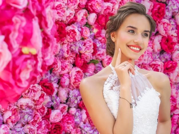 Schöne braut in einem hochzeitskleid, das mit dekorativen rosa blumen aufwirft