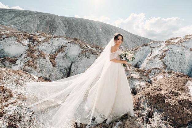 Schöne braut in einem hochzeitskleid mit einem blumenstrauß auf der spitze der salzberge.