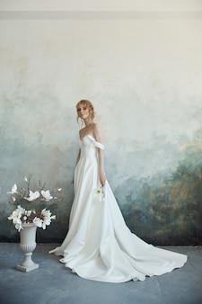 Schöne braut in einem langen weißen kleid