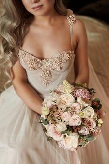Schöne braut in einem luxuriösen brautkleid mit einem brautstrauß mit pfingstrosen und rosenblüten