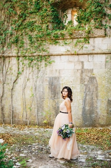 Schöne braut in einem pastellkleid geht mit einem luxuriösen blumenstrauß an der wand spazieren