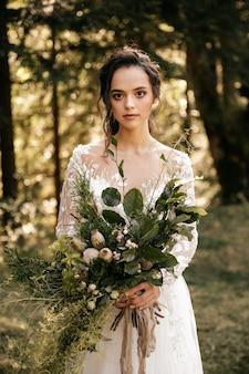 Schöne braut in einem weißen kleid mit einem blumenstrauß auf einem waldhintergrund