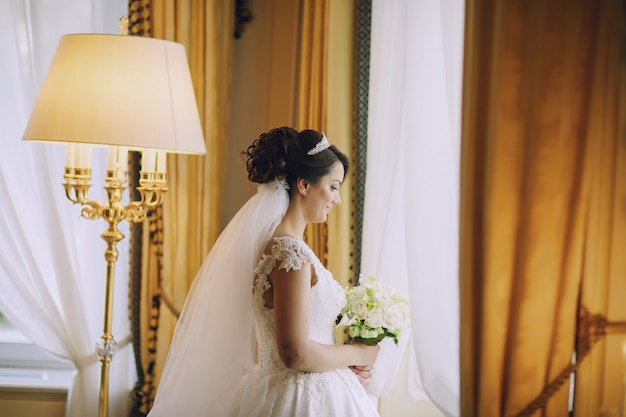 Schöne braut in einem weißen kleid und eine krone auf dem kopf und einen blumenstrauß