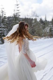 Schöne braut in ihrem hochzeitskleid im winter