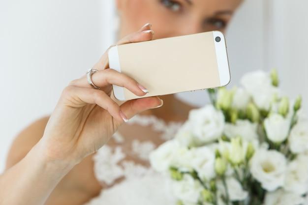 Schöne braut mit blumenstrauß und smartphone